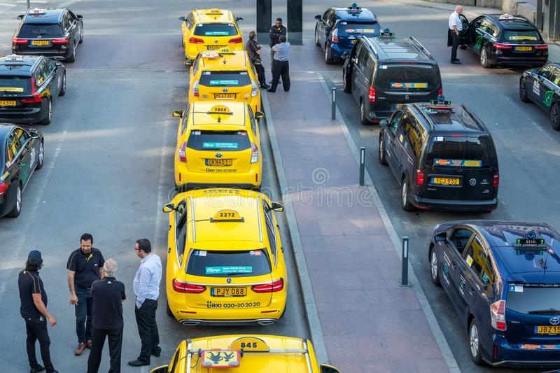 High angle city view of many yellow and black taxis in line. STOCKHOLM, SWEDEN - MAY 11, 2018: Horizontal high angle city view of many yellow and black taxis in stock photo