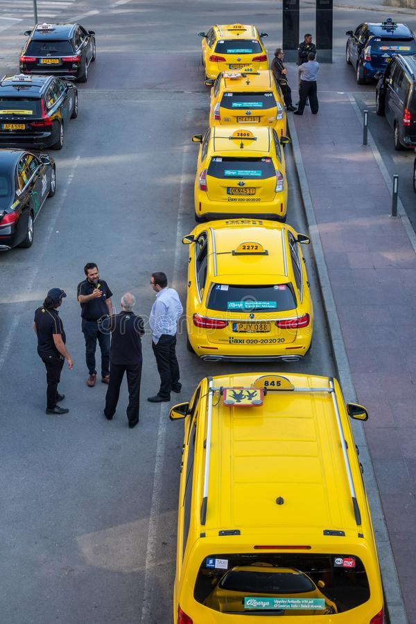 City view of many yellow and black taxis in line. STOCKHOLM, SWEDEN - MAY 11, 2018: Vertical high angle city view of many yellow and black taxis in line in the royalty free stock images