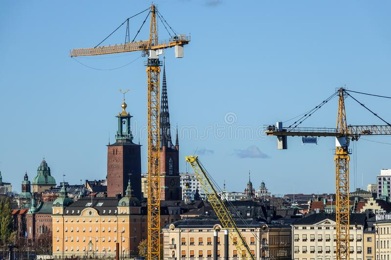 Rebuilding and tower cranes in fron of The Stockholm City Hall. Stockholm, Sweden - October 22, 2018: Rebuilding and tower cranes in fron of The Stockholm City stock image