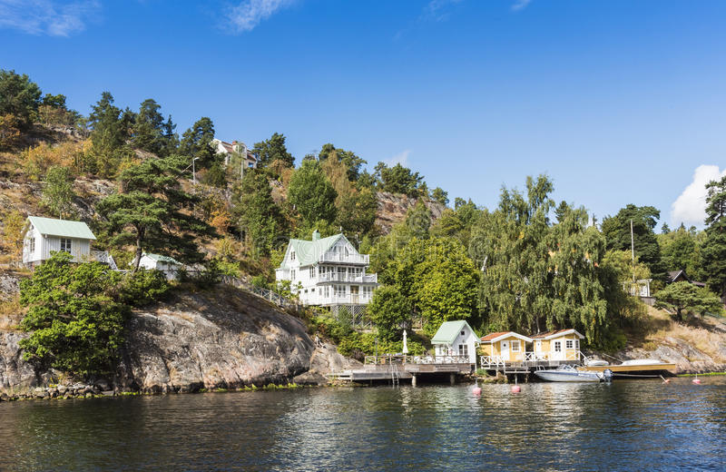 Stockholm by the water: Skurusundet Nacka. Waterside wooden houses and jetties with moored leisureboat in Nacka Björknäs a suburban residentual area at royalty free stock image