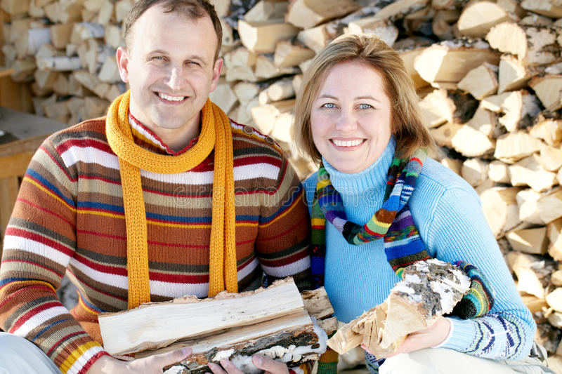 Stocking firewood. Portrait of mature couple stocking firewood, looking at camera and smiling stock images