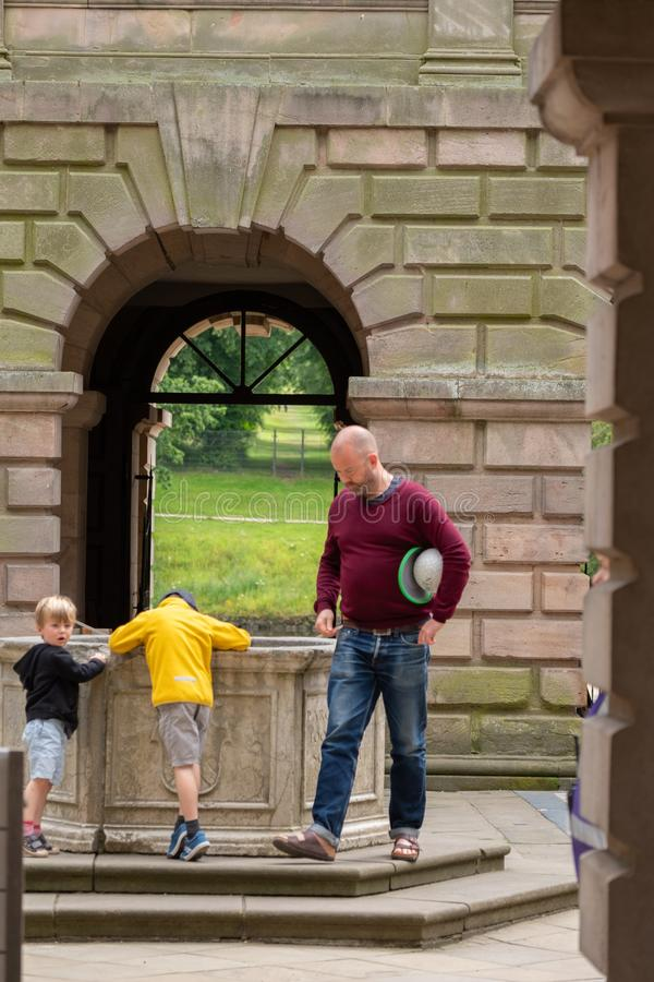 A father and his two boys stand by a pond at the endtrance of Lyme Hall, Lyme Hall historic English Stately Home and park in. Stockport, United Kingdom - July 21 stock images