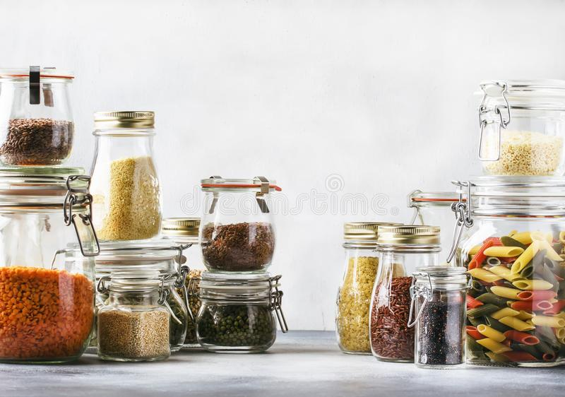 Stocks or set of cereals, pasta, groats, organic legumes and useful seeds in glass jars. Vegan source of protein and energy. Resources. Healthy vegetarian food stock photography