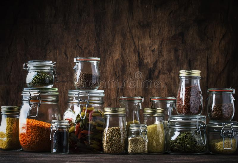 Stocks or set of cereals, pasta, groats, organic legumes and useful seeds in glass jars. Vegan source of protein and energy. Resources. Healthy vegetarian food stock images