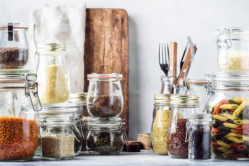 Stocks or set of cereals, pasta, groats, organic legumes and useful seeds in glass jars. Vegan source of protein and energy. Resources. Healthy vegetarian food royalty free stock photos