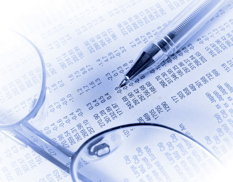 Stocks and shares. Reading glasses and pen on shares section of newspaper stock photo