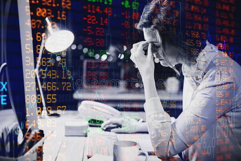Composite image of stocks and shares. Stocks and shares against stressed businesswoman sitting at desk stock photo