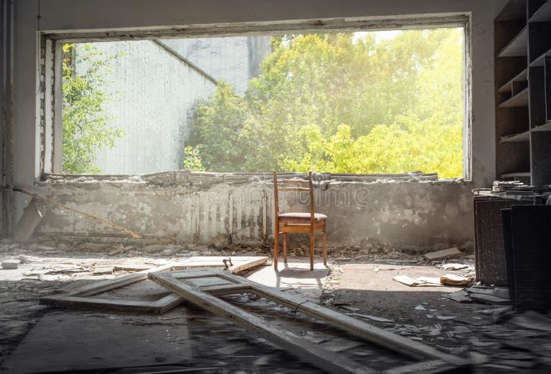 Stoel dichtbij het venster in vernietigde ruimte van de verlaten bouw in Pripyat, stock foto