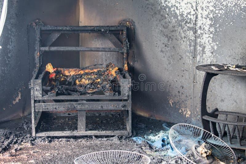 Stoel en meubilair in ruimte na gebrand door brand in brandwondscène o stock afbeeldingen