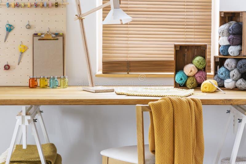 Stoel met gele deken bij bureau met lamp en kleurrijke garens in werkruimtebinnenland Echte foto royalty-vrije stock fotografie