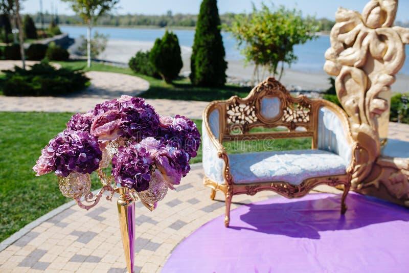 Stoel op de boog van de Huwelijksceremonie met gouden luxekader en purpere bloem en op rivieroever Bruid en bruidegomceremonie royalty-vrije stock fotografie