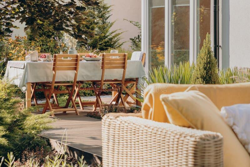 Stoelen bij lijst aangaande het terras van huis met installaties en rotanmeubilair tijdens de zomer Echte foto stock afbeelding