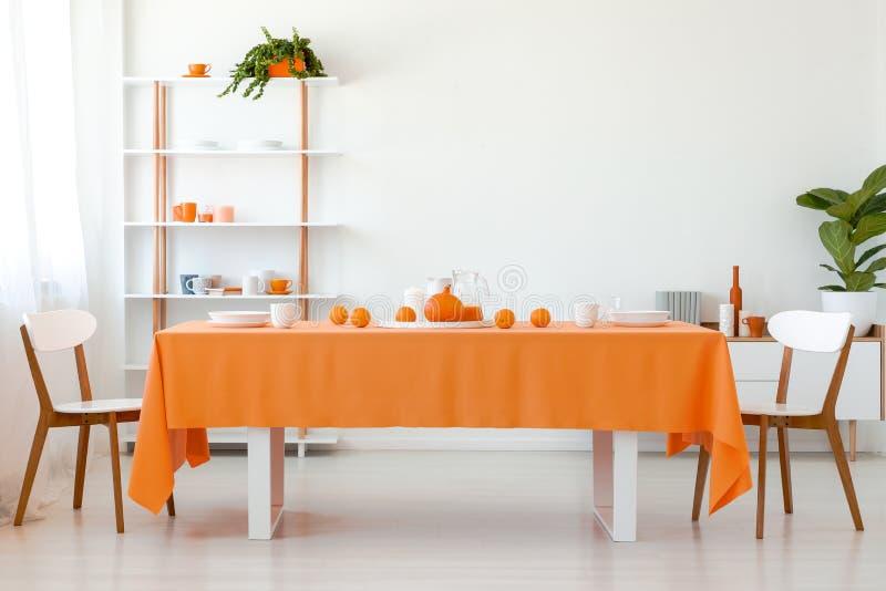 Stoelen bij lijst met oranje doek in wit eetkamerbinnenland met installatie op planken royalty-vrije stock afbeelding