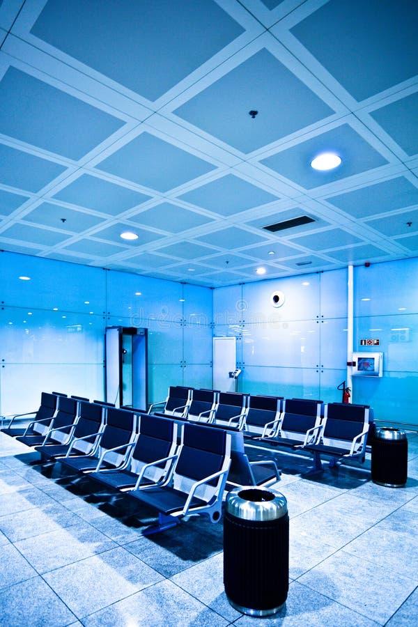 Stoelen in blauwe luchthavenzaal stock fotografie
