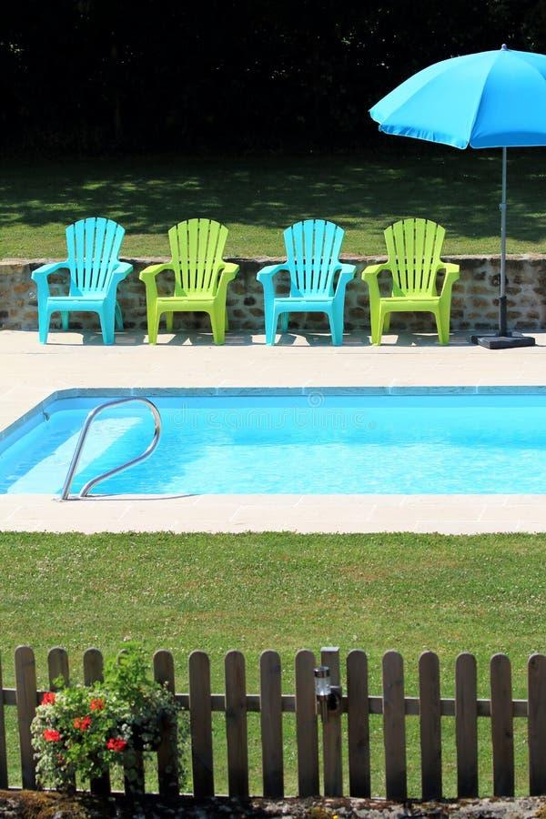 Stoelen door een pool stock afbeelding