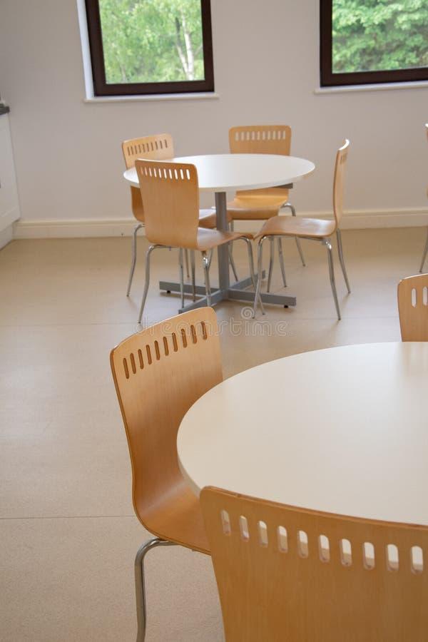 Stoelen en eiken houten lijst voor mensen die en lunch of diner verzamelen eten bij het werk in een bureaucafetaria stock foto