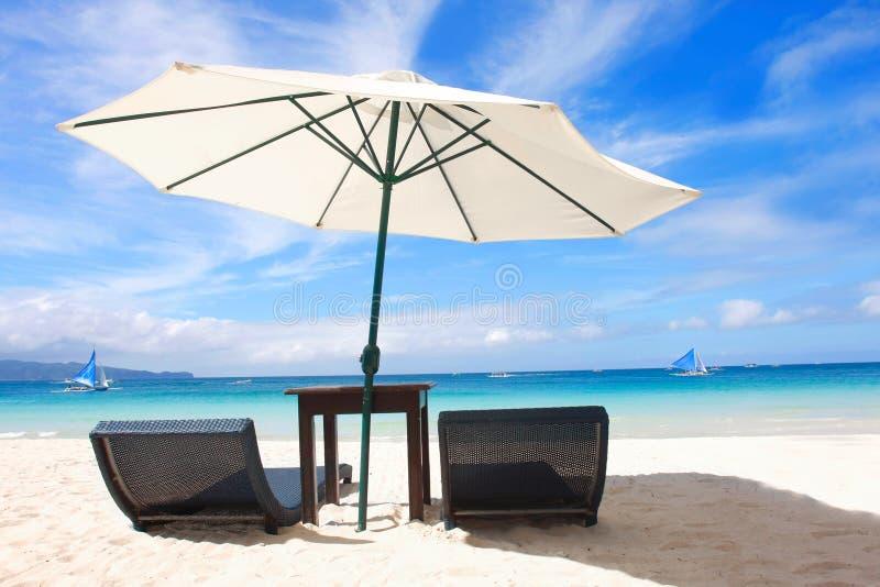 Stoelen en paraplu op strand stock afbeeldingen