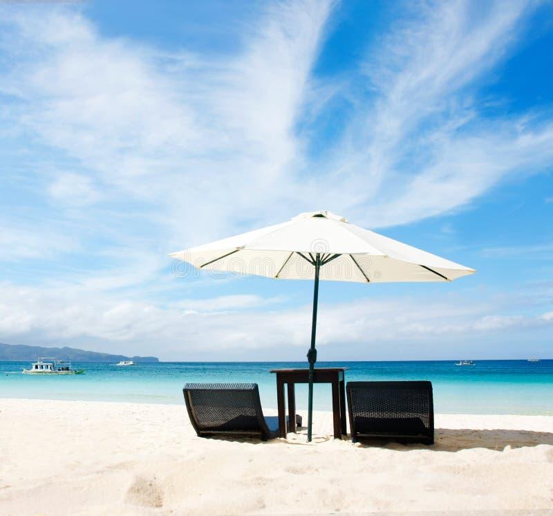 Stoelen en paraplu op strand royalty-vrije stock afbeeldingen