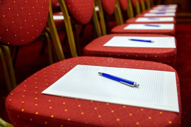 Stoelen met blocnotes en pennen in lege conferentieruimte royalty-vrije stock afbeelding