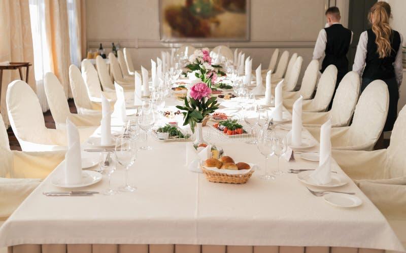 Stoelen met witte die doek en lijst voor gasten voor huwelijk worden gediend stock foto's