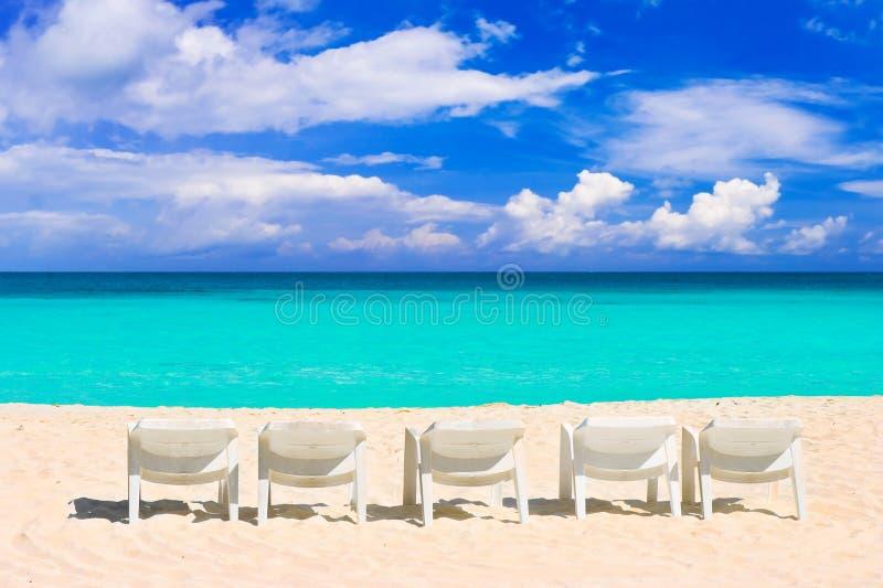 Stoelen op tropisch strand stock afbeelding