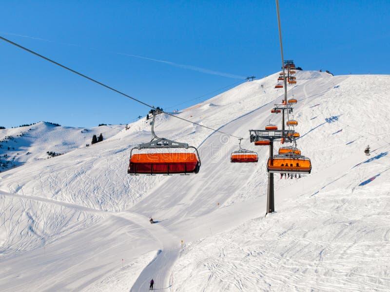 Stoelskilift met oranje bellenschuilplaats op zonnige de winterdag Witte sneeuw en duidelijke blauwe hemel in Saalbach Hinterglem royalty-vrije stock afbeelding