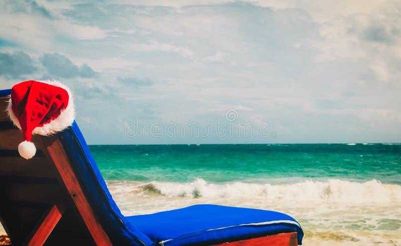 Stoelzitkamer met rode Kerstmanhoeden op tropisch strand royalty-vrije stock afbeeldingen