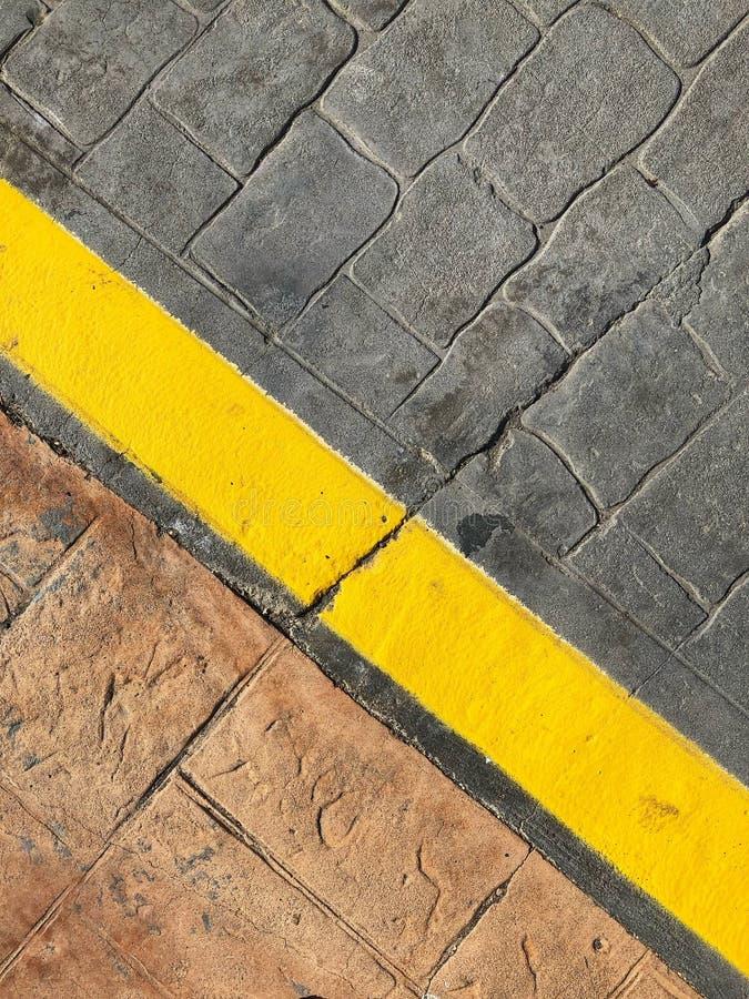 Stoepachtergrond - gele lijn op de grens van de wegstraat stock afbeeldingen