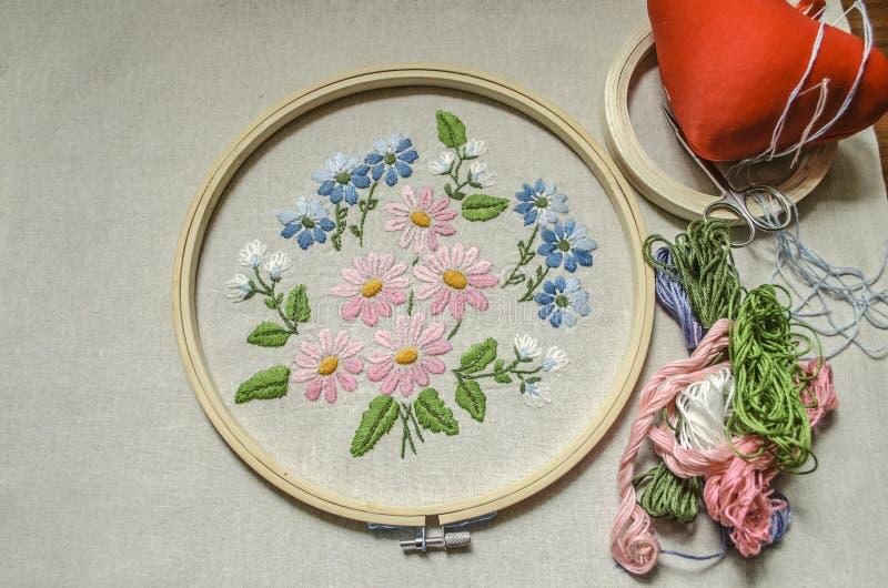 Stof met geborduurd die boeket van wildflowers met houten hoepels, gekleurde draden, schaar en een rood hoofdkussen voor naalden  stock foto's