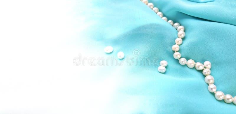 Stof van de Drapped de blauwe zijde met parelparels op witte achtergrond stock afbeeldingen