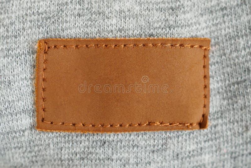 Stoffaufkleber des Brauns des freien Raumes lederner auf grauem Gewebe lizenzfreie stockbilder