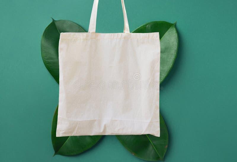 Stoffeinkaufstasche des leeren weißen Modells Leinenbaumwollauf grünem Blattlaubhintergrund Freundliche Materialien der null ?ber stockbilder
