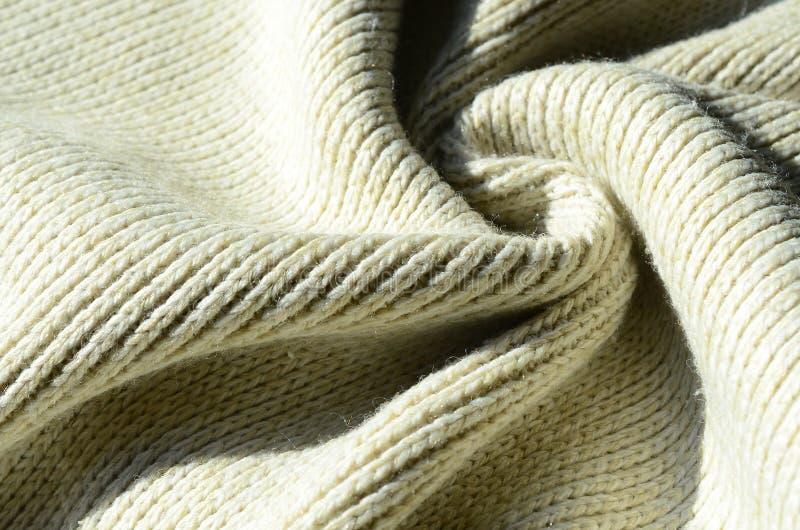 Stoffentextuur van een zachte gele gebreide sweater Macrobeeld van de structuur van banden in garens royalty-vrije stock foto's