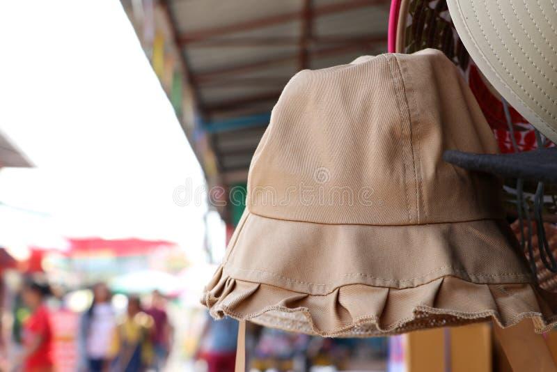 Stoffhut oder Gewebehut in der braunen Farbe, die am Hutaufhänger für Verkauf hängt stockbild