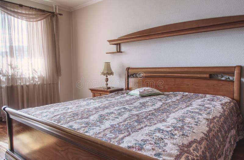 Stoffig nam hoofdslaapkamer met klassiek houten meubilair toe stock foto's