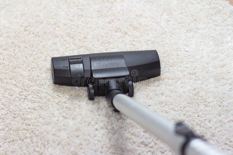 Stofzuiger die worden gebruikt om een tapijt om te zuigen stock afbeelding