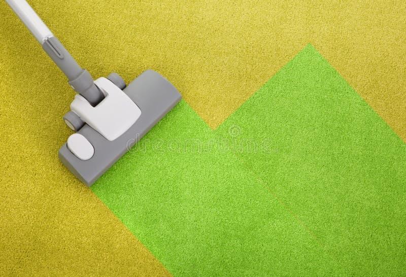 Stofzuiger op een groen tapijt stock foto