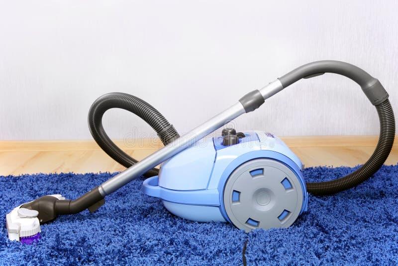 Stofzuigertribune op blauw tapijt. royalty-vrije stock afbeelding