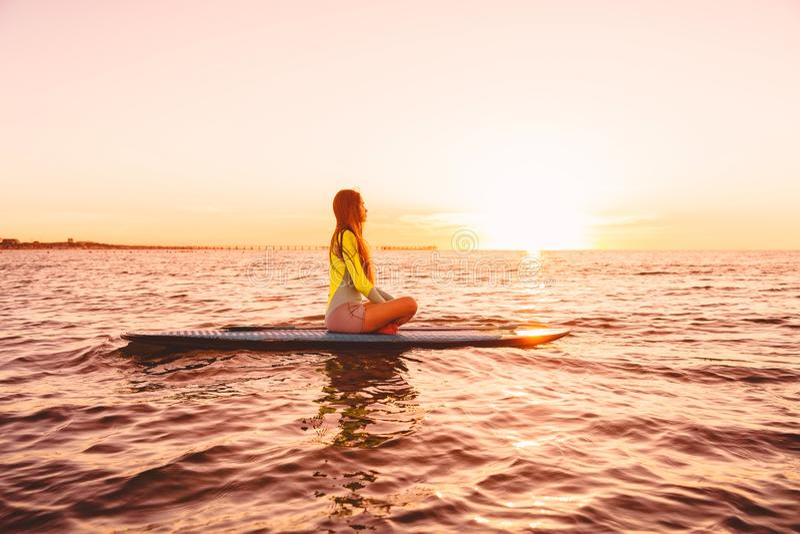 Stoi up paddle abordaż na spokojnym morzu z zmierzchów kolorami Kobieta na SUP desce zdjęcia stock
