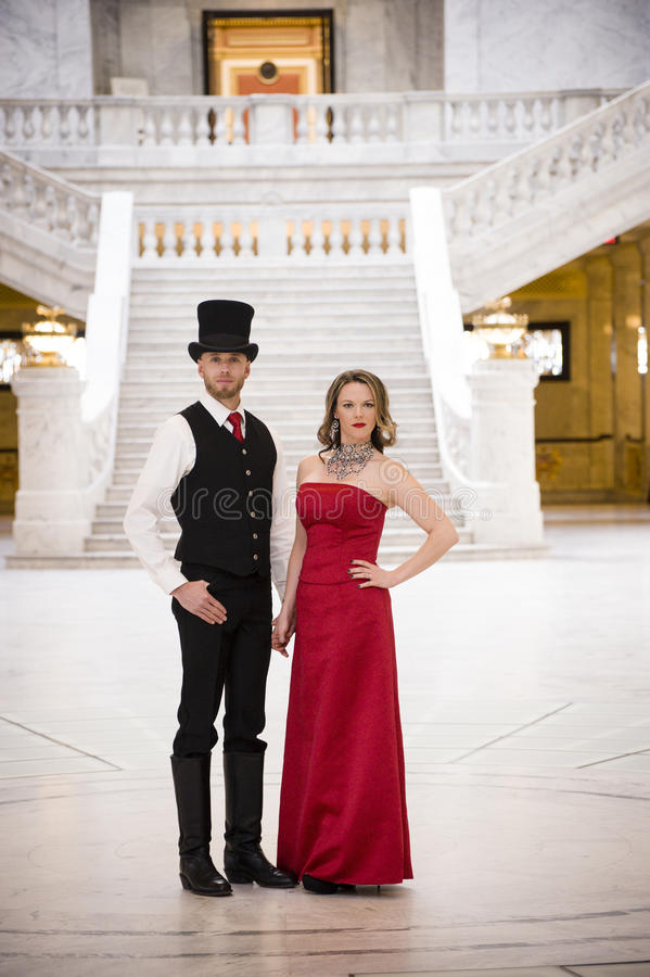 Stoic Couple. Timeless couple in front of a grand staircase stock image