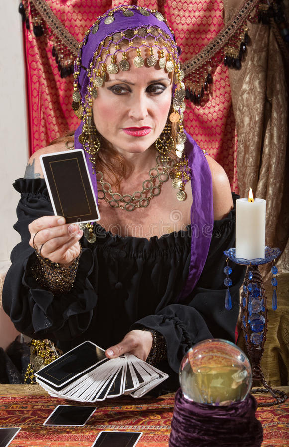Stoic Fortune Teller. Stoic Roma lady looking at a tarot card indoors stock photography