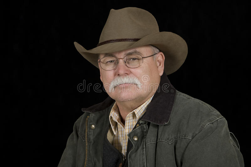 Stoic Looking Cowboy. This man in his 50s who is wearing traditional western wear has a stoic expression stock photography