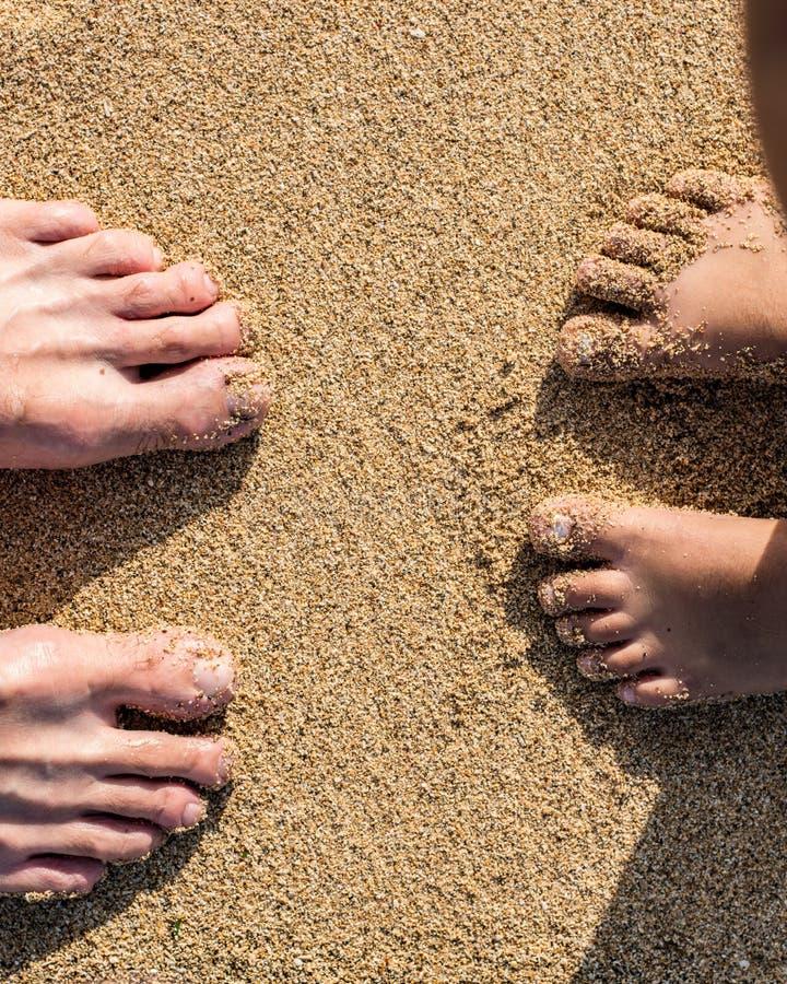 Stojący na piasku patrzeje puszek przy ciekami, dzieckiem i ojcem, przy plażą zdjęcia royalty free