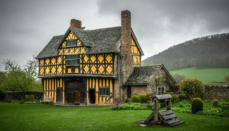 Stokesay castle gatehouse with yellow color and half-timbered detailing and view of garden on an overcast day. Stokesay castle gatehouse in Shropshire England stock photos