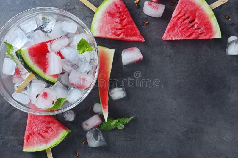 Stokken met watermeloenplakken en ijsblokjes op lijst royalty-vrije stock foto