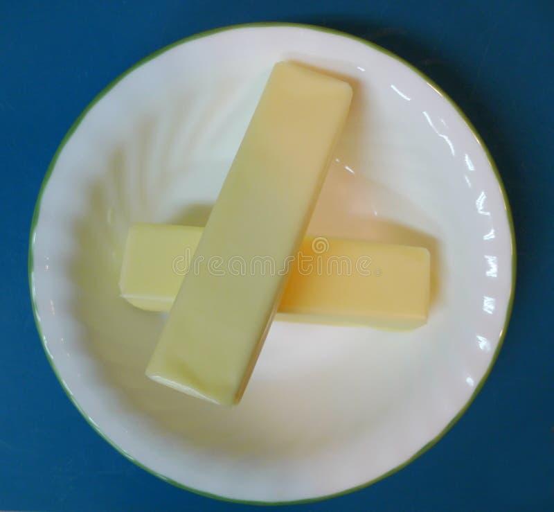 Stokken van boter in een witte kom op een blauwe achtergrond stock fotografie
