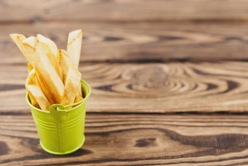 Stokken van frieten in groene kleine metaalemmer met handvat op oude houten rustieke bruine planken stock afbeelding