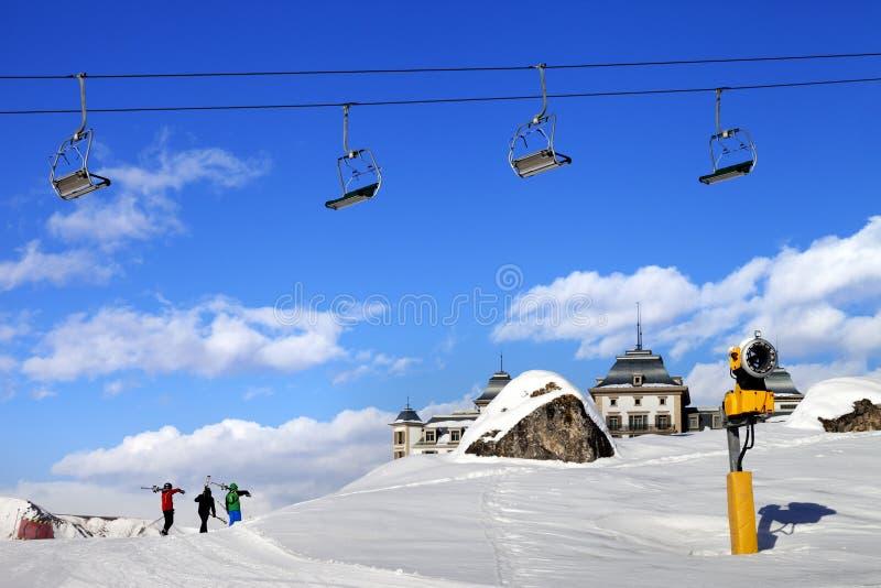 Stol-elevatorn i blå himmel och tre skidåkare skidar på lutningen på den trevliga solen royaltyfria bilder