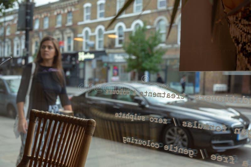 Stol i frisör shoppar tomt och i kvinnan för bakgrund som en inom passerar och ser London royaltyfria bilder