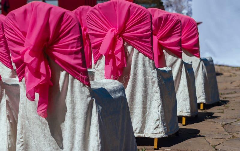 Stolar för gäster på bröllopceremoni med vit och rosa satäng royaltyfri bild